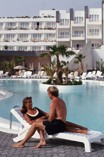 Girl lying on sun lounger with man sitting next to her, by swimming pool : Stock Photo