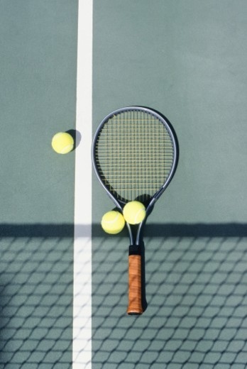 Stock Photo: 1598R-97133 Tennis racket and balls lying on court