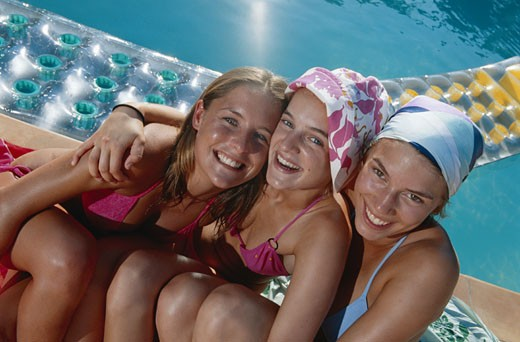Teenage girls near swimming pool, laughing : Stock Photo