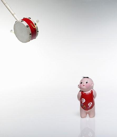Chinese ceramic figurine and swinging drum, studio shot : Stock Photo