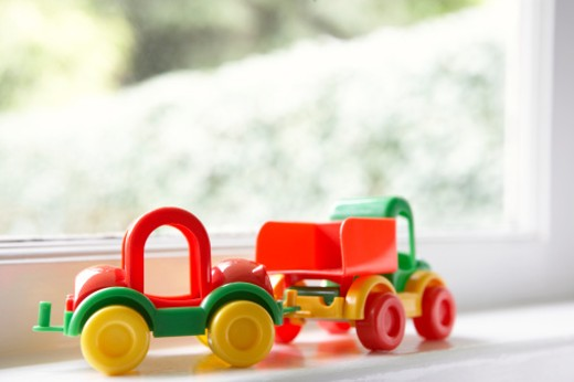 Plastic toy truck on window sill : Stock Photo