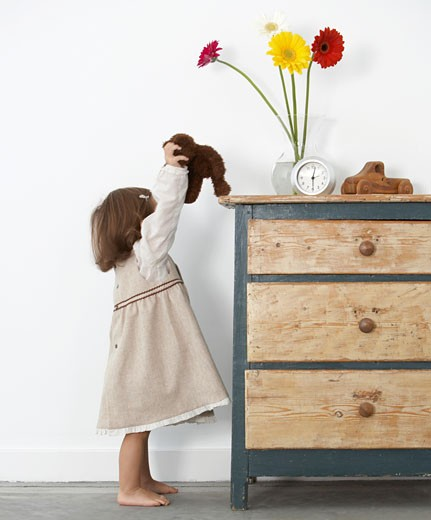 Stock Photo: 1598R-9939562 Toddler girl (18-21 months) setting teddy bear atop dresser, side view