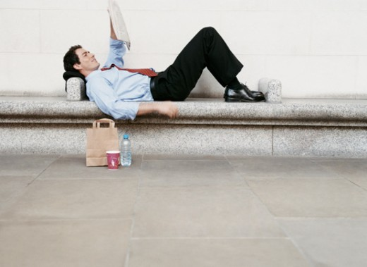 Businessman Lying on a Stone Bench, Reading a Newspaper : Stock Photo