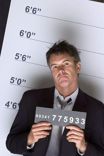 Portrait of a Tough Criminal Businessman Holding an Identity Card in a Police Line Up : Stock Photo