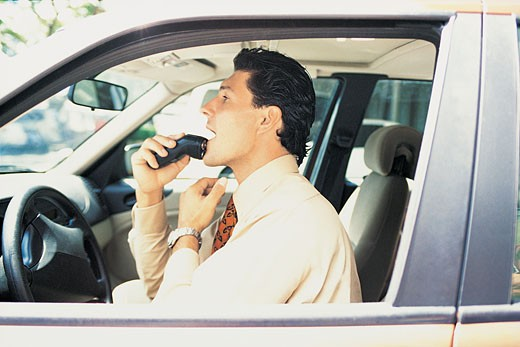 Stock Photo: 1598R-9939866 Businessman Using an Electric Razor in the Front Seat of His Car