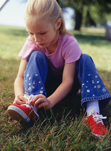 Girl (4-5) tying tennis shoes in park : Stock Photo