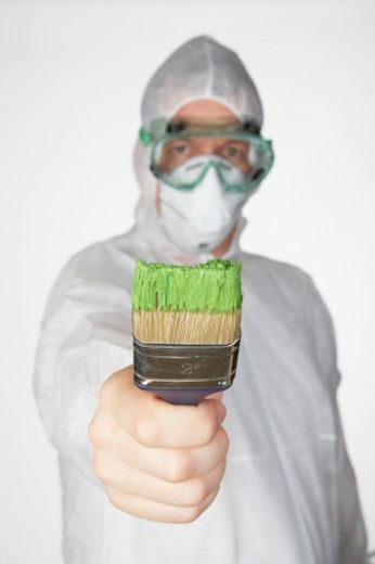 Stock Photo: 1598R-9940576 Man wearing safety mask and goggles holding paintbrush, focus on brush, portrait