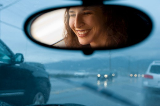 Woman driving car in rain, view from rearview mirror : Stock Photo