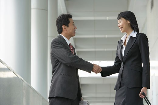 Businesswoman and businessman shaking hands in corridor : Stock Photo