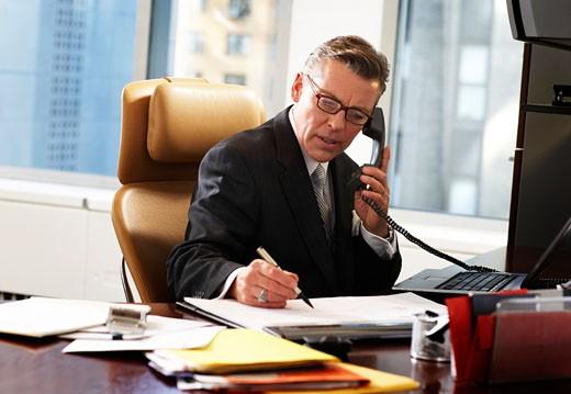 Stock Photo: 1598R-9940962 Businessman at desk using telephone, writing