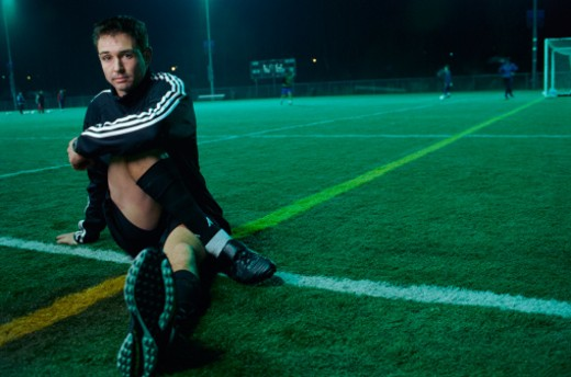 Portrait of a Man Sitting Down at the Edge of a Football Pitch : Stock Photo