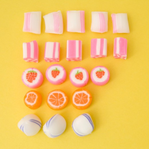 Stock Photo: 1598R-9941049 Five rows of candy on yellow background