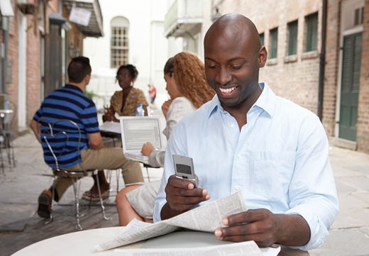 Young man using mobile phone in outdoor cafe, smiling : Stock Photo