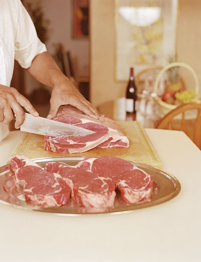 Man Slicing Steak on a Chopping Board in the Kitchen : Stock Photo
