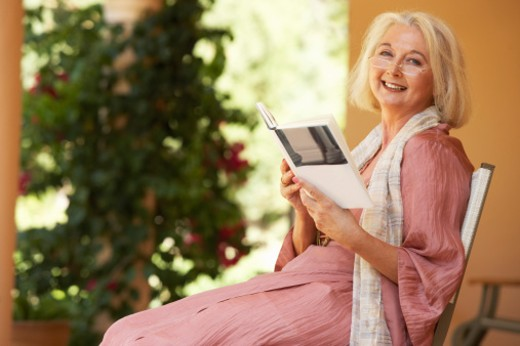 Senior woman on chair holding book, smiling, portrait : Stock Photo