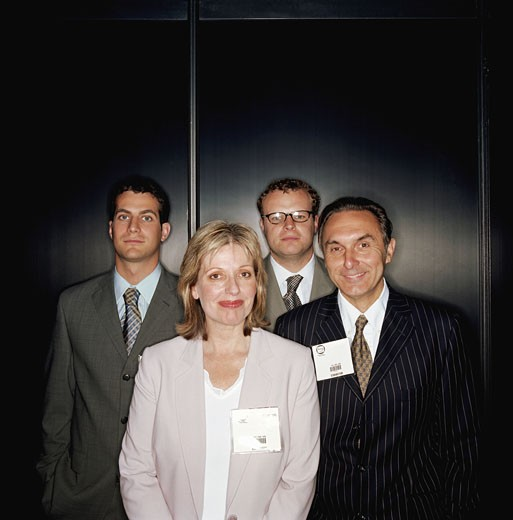 Four business people standing by wall, smiling, portrait : Stock Photo