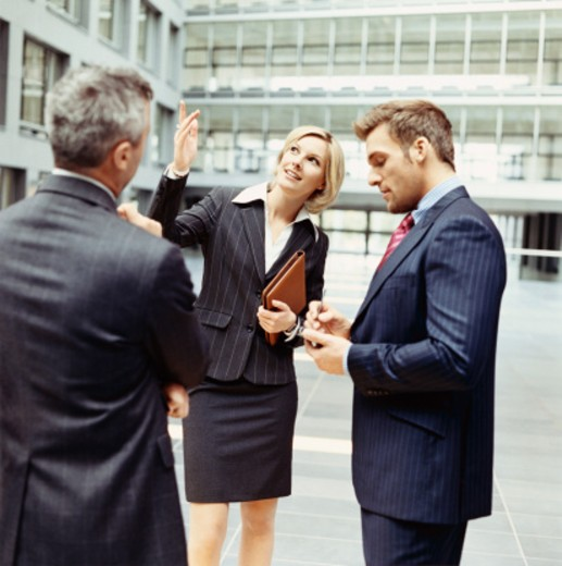 Stock Photo: 1598R-9942004 Businesswoman Shows Two Businessmen Around a Lobby, One of the Businessmen Uses His Handheld PC
