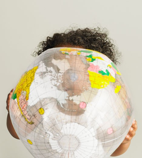Baby girl (15-18 months) holding inflatable globe : Stock Photo