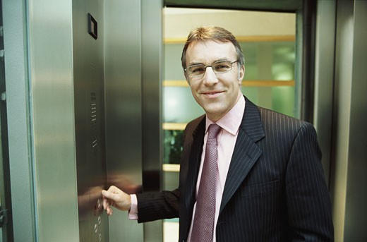 Businessman Standing in an Elevator Pressing a Button : Stock Photo