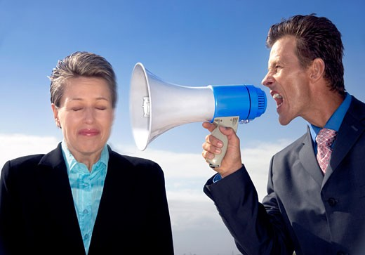 Businessman Shouting at a Businesswoman Through a Megaphone : Stock Photo