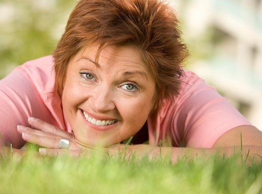 Mature woman lying on lawn smiling, close up, portrait, surface level : Stock Photo