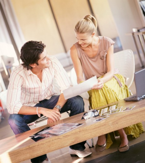 Stock Photo: 1598R-9943003 Model and Photographer Sit Side by Side in an Office Discussing Photos from a Shoot