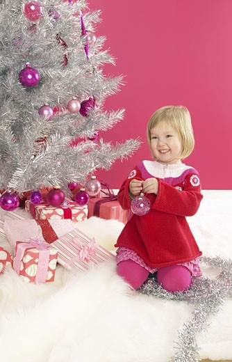 Young Girl Decorating an Artificial Christmas Tree : Stock Photo