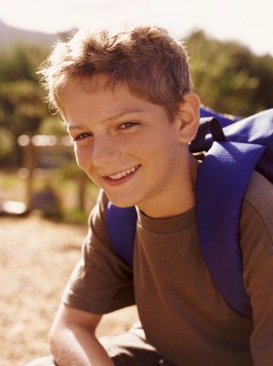 Boy Sitting in the Countryside Wearing a Rucksack : Stock Photo