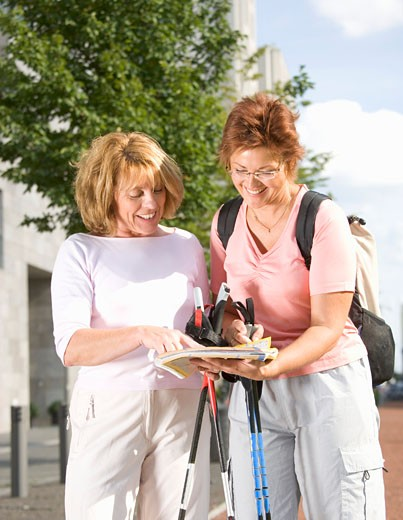 Two mature women looking at map and holding walking sticks : Stock Photo