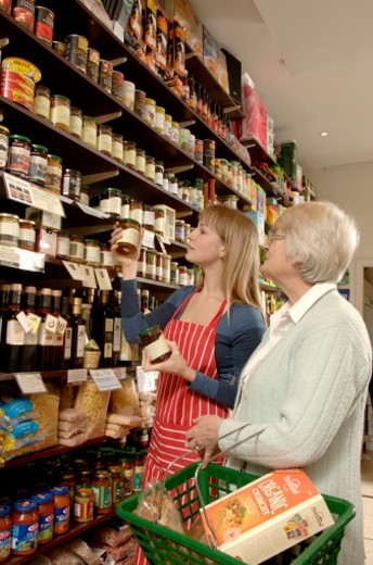 Shop assistant in delicatessen helping female customer select groceries : Stock Photo