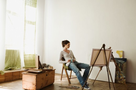 Stock Photo: 1598R-9944450 Woman sitting at easel in studio
