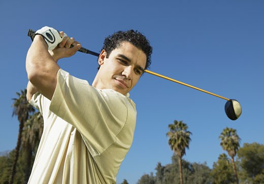 Stock Photo: 1598R-9944674 Man Swings a Golf Club, Looking Down in Concentration