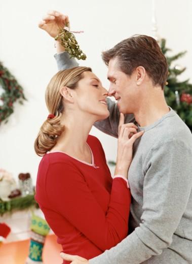 Adoring Couple Underneath Mistletoe : Stock Photo