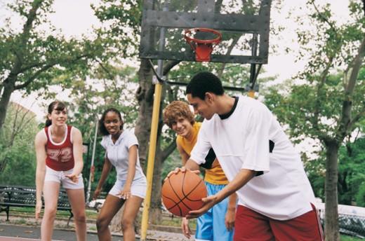 Stock Photo: 1598R-9945000 Teenage Girls and Boys Playing Basketball