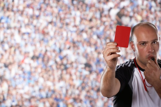 Referee holding up red card on field : Stock Photo