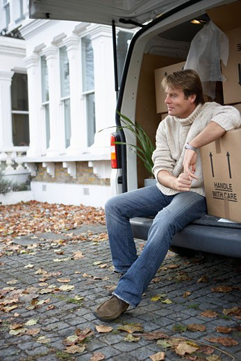 Mature man sitting in back of van looking away : Stock Photo