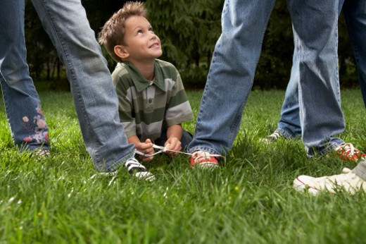 Stock Photo: 1598R-9945310 Boy (8-9) lying among children (10-11, 12-13), tying shoelaces of two children together, on lawn
