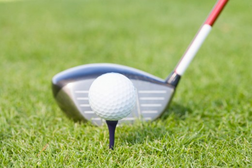 Stock Photo: 1598R-9945340 Golf club behind golf ball on tee, close-up