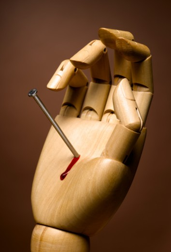 Wooden hand with nail in it, bleeding, close-up : Stock Photo