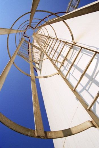 Stock Photo: 1598R-9946135 Caged ladder on tower at oil refinery plant, low angle view