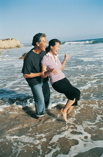 Stock Photo: 1598R-9946153 Mature Couple Messing About on a Beach at the Waters Edge