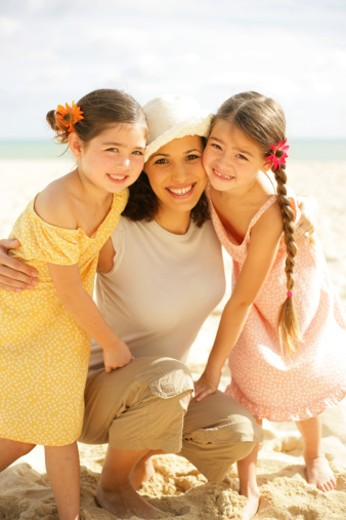 Mother with two daughters (6-8) on beach, smiling, portrait : Stock Photo