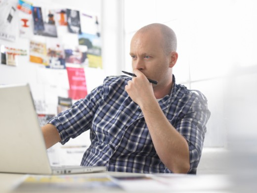 Man using laptop in design studio : Stock Photo