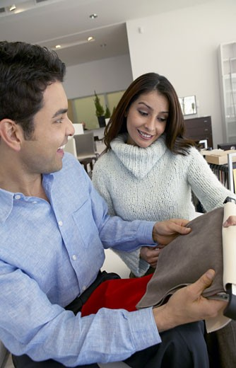 Couple in a Home Interior Shop Choosing From Fabric Samples : Stock Photo
