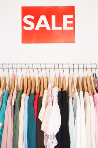 Clothes hanging on rail, sale signs on wall : Stock Photo
