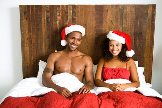 Portrait of young couple wearing santa hats in bed : Stock Photo