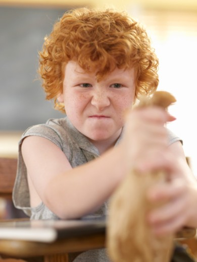 Stock Photo: 1598R-9947352 Angry boy (9-11) sitting in classroom, holding paper bag