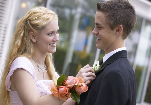 Stock Photo: 1598R-9947379 Young Couple Standing Face to Face Dressed for a High School Prom, Girl Adjusting Boy's Corsage
