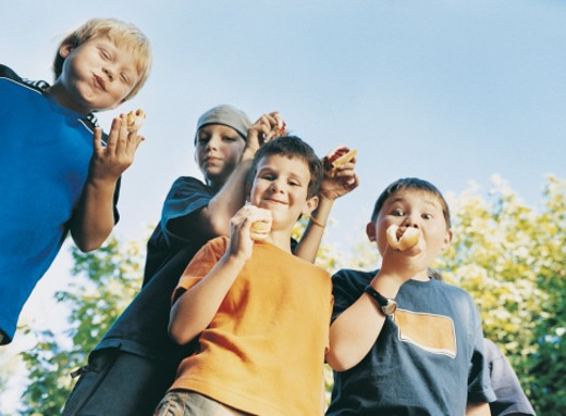 Four Boys Pulling Faces as They Eat Hotdogs : Stock Photo