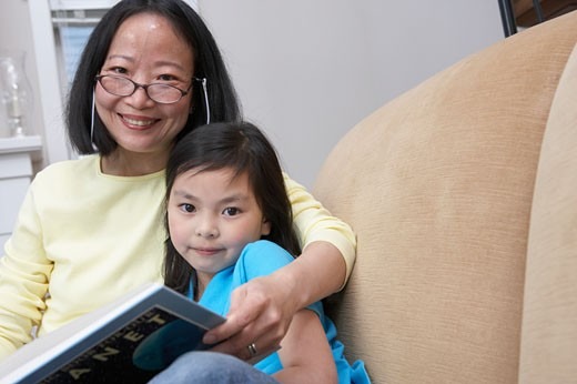 Portrait of a Woman Sitting in a Chair Reading a Book With Her Young Daughter : Stock Photo
